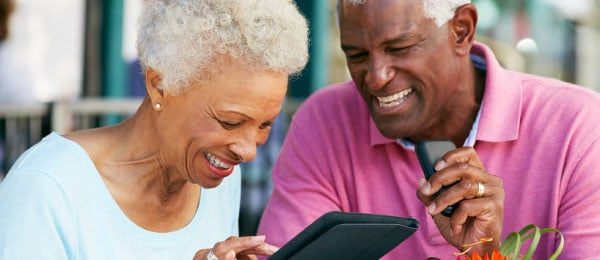 an elderly couple using a tablet