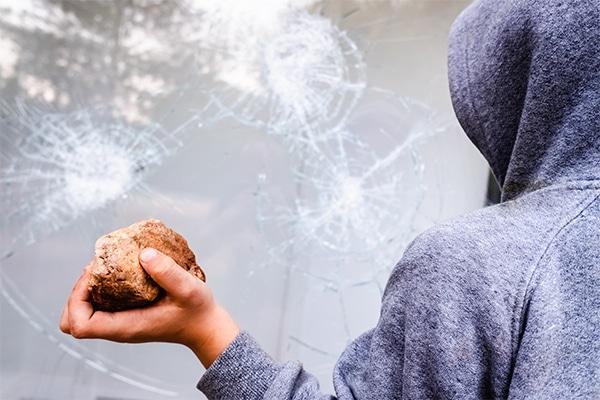 a burglar breaks a glass window