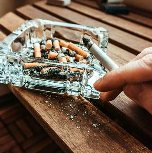 a person ashes their cigarette in an ashtray